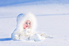 Baby in snow. Cute little baby in a white jacket playing in snow Royalty Free Stock Photos