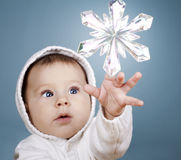 Baby with snow flake. Beautiful baby girl is playing with snow flake ornament Royalty Free Stock Image