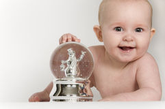 Baby and Snow Globe. Baby on tummy with hand on snow globe, smiling at the camera. Copy Space Stock Photo