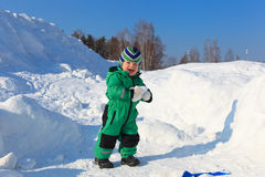 Baby snow joy. 1.5 year old boy building from snow in winter nature Stock Photos
