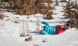 Baby in snow. Little baby girl playing and having fun in the snow, during the winter holidays Stock Photo
