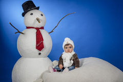Baby with snowman. Wing is a baby sitting next to a snowman Royalty Free Stock Photo