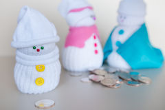 Baby snowman looks at a coin Stock Photography