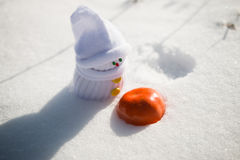 Baby-snowman looks at a tangerine Stock Photos