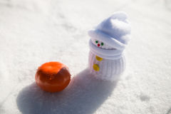 Baby-snowman and a tangerine. Baby-snowman looks at a tangerine Stock Photography