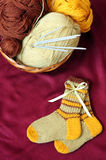 Baby socks. Stripy handmade woolen baby socks, wool yarns and knitting needles in  basket Royalty Free Stock Images