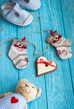 Baby socks on clothes line, gingerbread heart and blue shoes Stock Image