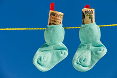 Baby socks on clothesline with yen banknotes Royalty Free Stock Images
