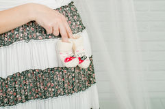 Baby socks in  hands of pregnant woman Stock Photos