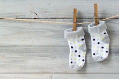 Baby socks hanging on clothesline on wooden background royalty free stock photography
