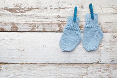 Baby socks hanging on white wooden background. Flat lay Royalty Free Stock Photography