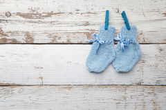 Baby socks hanging on white wooden background. Flat lay Royalty Free Stock Images