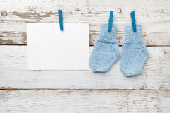 Baby socks hanging on white wooden background. Flat lay Royalty Free Stock Photo