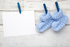 Baby socks hanging on white wooden background. Flat lay Royalty Free Stock Image