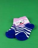 Baby socks on isolated green Stock Photos