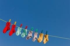 Baby socks on laundry. Baby socks on clothesline to dry. Blue sky stock photo