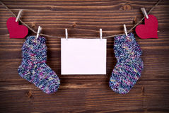 Baby Socks on a Line with Hearts and an Banner with Copy Space Royalty Free Stock Image