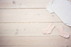 Baby socks and shirt. On light wooden table. Mock up Stock Images