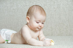 Baby on sofa looking at sock Stock Photography