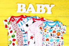 Baby soft fashion clothes background. Infants collection of rompers, word baby on yellow wooden background royalty free stock photo