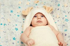Baby in soft pajamas. Top view of cute little baby lying in soft pajamas with ears on the bed stock images