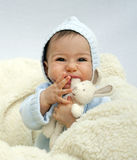 Baby with a soft toy. Portrait of a baby sitting on sheep skin playing with of soft toys rabbit; the child is hugging and biting the toy royalty free stock photos