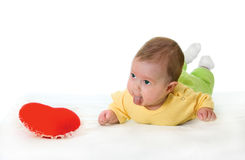 Baby with a soft toy in the form of heart Stock Image