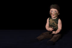 Baby soldier in uniform with war paint on his face. Boy in unifo Royalty Free Stock Photos