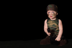 Baby soldier in uniform with war paint on his face. Boy in unifo Stock Photo