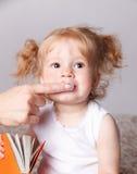Baby som får hennes tänder, gjorde ren med fingertandborsten Arkivbild