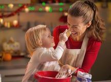 Baby som försöker att sudda mödrar, nose med mjöl, medan göra kakor Royaltyfria Bilder