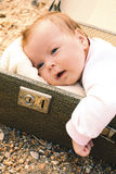 Baby som ligger i en resväska Arkivbilder