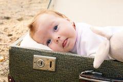 Baby som ligger i en resväska Fotografering för Bildbyråer