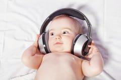 Baby som ligger lyssna ner till musik med trådlös hörlurar. fotografering för bildbyråer