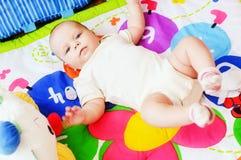 Baby som ligger på den framkallande filten arkivbild