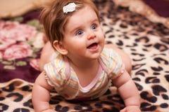 Baby som ligger på en filt Arkivbild