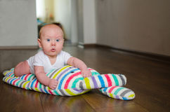 Baby som ligger på en plysch, brokig kanin på golvet Fotografering för Bildbyråer