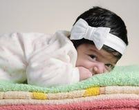 Baby som ligger på en towe Arkivbild