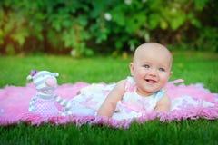 Baby som ligger på grönt gräs i parkera Arkivfoton
