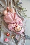 Baby som ligger på linnefilten och bär en hatt i form av en påskkanin med äggpilfilialer och påskpajen arkivbilder