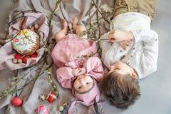 Baby som ligger på linnefilten och bär en hatt i form av en påskkanin med hennes broder nära äggpilfilialer royaltyfria bilder