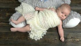 Baby som ligger på träbakgrund arkivfilmer