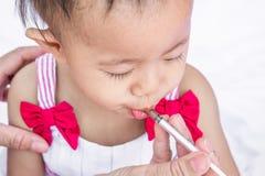 Baby som matar med vätskemedicin med en injektionsspruta royaltyfria bilder