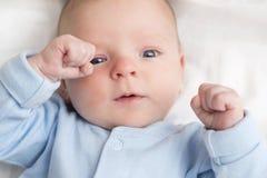 Baby som ner ligger p? tillbaka lyckligt litet barn i bodysuiten som ser upp St?enden av ett gulligt behandla som ett barn att li arkivbilder