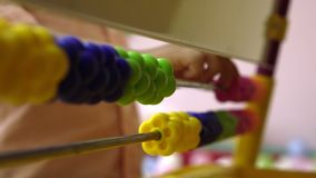 Baby som räknar på kulrammet som spelar leken i daycare med finansiella hjälpmedel, slut för elementär utbildning upp arkivfilmer