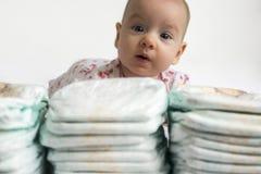 Baby som ser över en bunt av blöjor arkivfoton