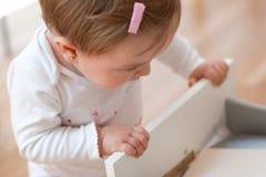 Baby som ser inom en enhet royaltyfria bilder