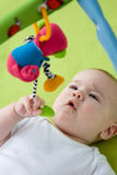 Baby som ser upp på en mobil toy Royaltyfria Bilder