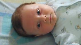Baby som ser upp på en mobil toy lager videofilmer