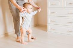 Baby som tar första steg med moderhjälp Arkivbild